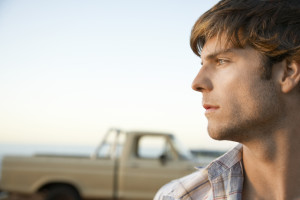 Closeup of thoughtful young man with pick-up truck in background
