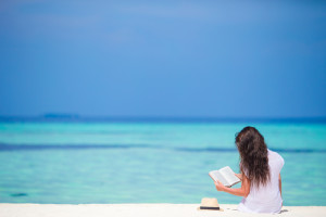 dreamstime_s_57751731 girl on beach reading