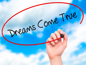 Man Hand writing Dreams Come True with black marker on visual screen. Business, technology, internet concept.