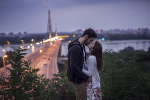 Young couple kissing each other in front of the city lights. High ISO, grainy image.
